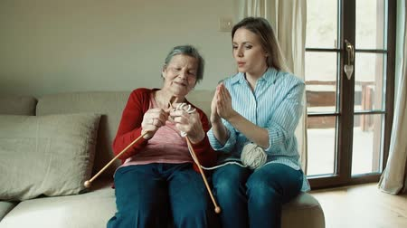 dziadkowie : Elderly grandmother and adult granddaughter at home, knitting.