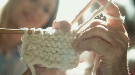 vrásčitý : Unrecognizable grandmother and granddaughter at home, knitting. Close up.