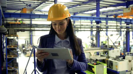An industrial woman engineer in a factory standing with tablet, working.