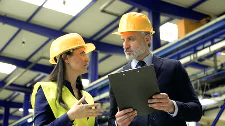 шлем : Industrial man and woman engineers with clipboard in a factory, talking. Стоковые видеозаписи