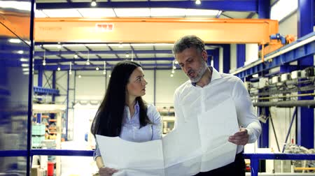 supervisor : Industrial man and woman engineers looking at blueprints.
