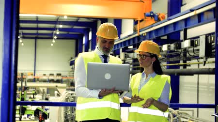 yelek : Industrial man and woman engineers with laptop in a factory, working.