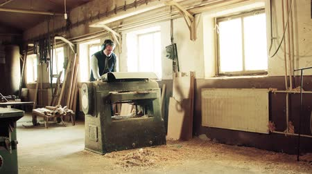 raw materials : A man worker in the carpentry workshop, working with wood. Stock Footage