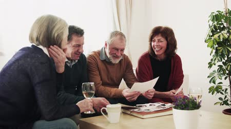 white wine : Two senior couples looking at photographs at home. Stock Footage