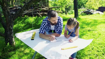 feeder : Father with a small daughter outside, planning wooden birdhouse.