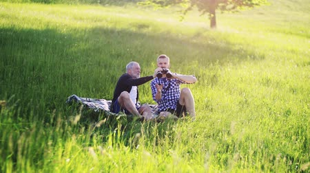 checked pattern : An adult hipster son and senior father with binoculars sitting on the grass in sunny nature.
