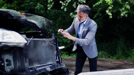 evidência : Mature man taking pictures of a broken car after an accident.