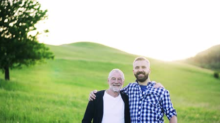 checked pattern : A portrait of an adult hipster son with senior father in nature at sunset, arms around each other. Stock Footage