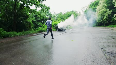 after fire : A mature man running towards the car in fire after an accident.