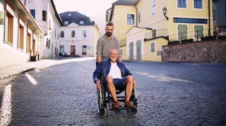 checked pattern : An adult son with senior father in wheelchair on a walk in small town.
