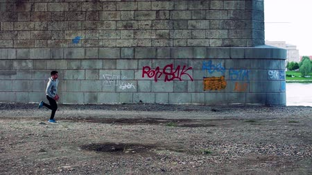 grafiti : Young athlete running by the river under the bridge in the city.