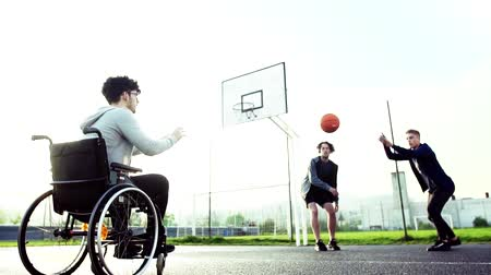 rokkant : A boy in wheelchair with teenager friends outside playing basketball. Stock mozgókép
