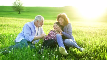 grandad : Senior couple with granddaughter sitting outside in spring nature at sunset.