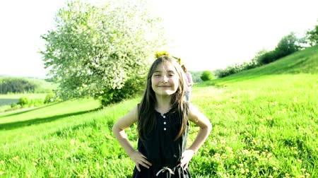 grandad : A small girl with dandelion wreath on her head walking outside in spring nature. Stock Footage