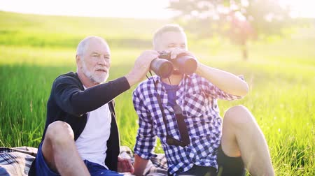 checked pattern : An adult son and senior father with binoculars sitting on the grass in nature.