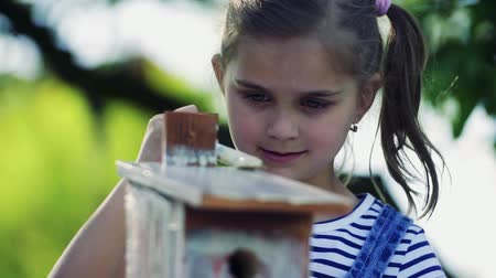 besleyici : A small girl outside, painting a wooden birdhouse.
