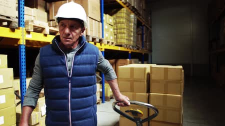 hard hat : Senior male warehouse worker pulling a pallet truck. Stock Footage