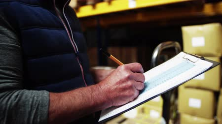 отправка : An unrecognizable senior male warehouse worker or a supervisor, writing.