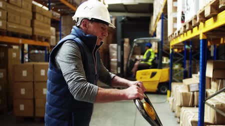 отправка : Senior male warehouse worker with a pallet truck, working.