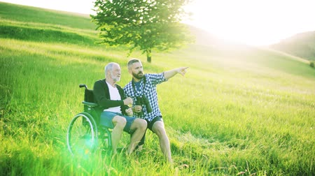 checked pattern : A hipster son and senior father in wheelchair using binoculars in nature at sunset. Stock Footage