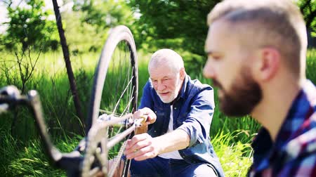 cadeia : An adult hipster son and senior father repairing bicycle outside on a sunny day.