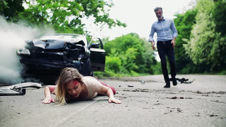 after fire : A man running towards a young woman lying on the road after a car accident.