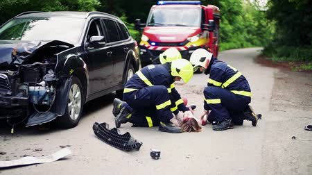 ölümcül : Firefighters rescuing a young injured woman lying on the road after an accident. Stok Video