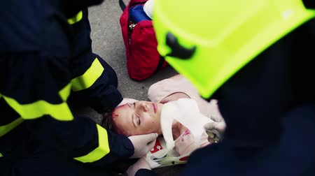 ilk yardım : Firefighters rescuing a young injured woman lying on the road after an accident. Stok Video