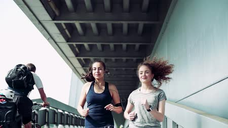 футболки : Young girls with smartwatch and smartphone running outdoors, under a bridge.
