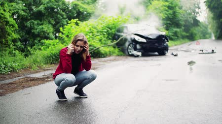 squat : Young woman making a phone call after a car accident, smoke in the background. Stock Footage