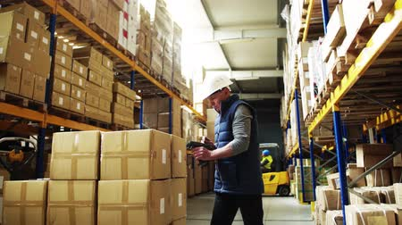 kod kreskowy : Portrait of a senior male warehouse worker or a supervisor using barcode scanner.