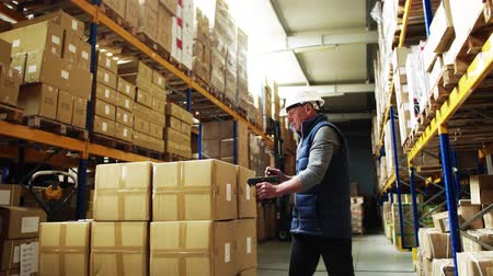 odeslání : Portrait of a senior male warehouse worker or a supervisor using barcode scanner.