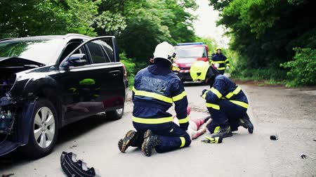 salva vidas : Firefighters rescuing a young injured woman lying on the road after an accident. Vídeos