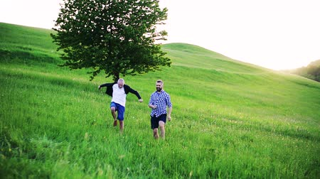 checked pattern : An adult hipster son with senior father running and jumping in nature.