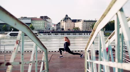перила : Beautiful young woman stretching by the river in the city.