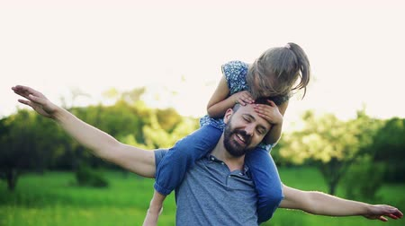 prole : Father giving small daughter a piggyback ride in spring nature at sunset. Stock Footage