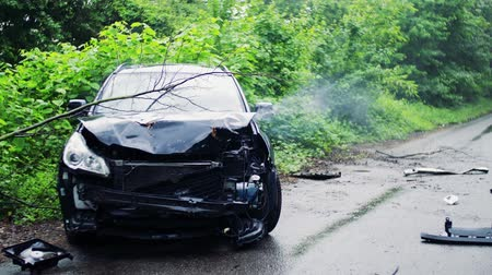 vrak : A broken car after an accident, smoke coming out from under the hood. Dostupné videozáznamy