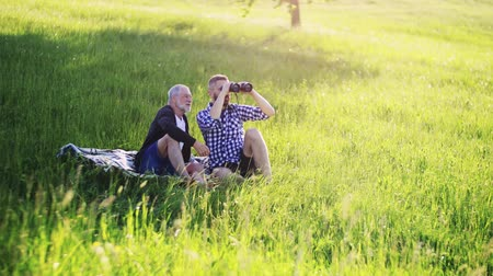 checked pattern : An adult hipster son and senior father with binoculars sitting on the grass at sunset.