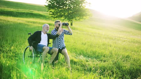 checked pattern : An adult hipster son with binoculars and senior father in wheelchair in sunny nature.