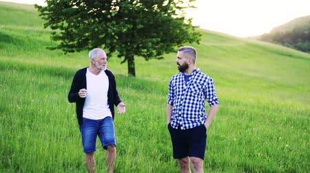 checked pattern : An adult hipster son with senior father walking in nature at sunset.