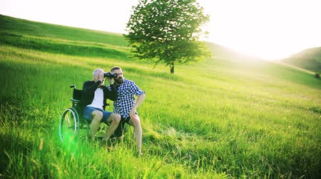 checked pattern : A hipster son and senior father in wheelchair using binoculars at sunset in nature. Stock Footage
