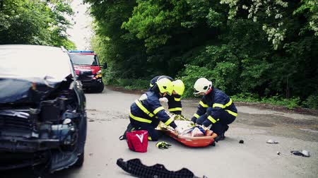 salva vidas : Firefighters helping a young injured woman after a car accident.