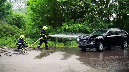 extinguishing : Two firefighters extinguishing a burning car after an accident. Stock Footage