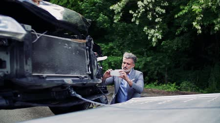 carro attrezzi : Mature man taking pictures of a broken car after an accident.