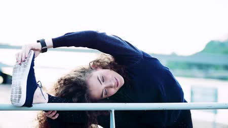 перила : Beautiful young woman stretching legs on the railing in the city. Стоковые видеозаписи