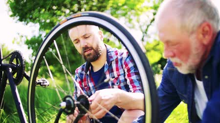 checked pattern : An adult hipster son and senior father repairing bicycle outside on a sunny day.
