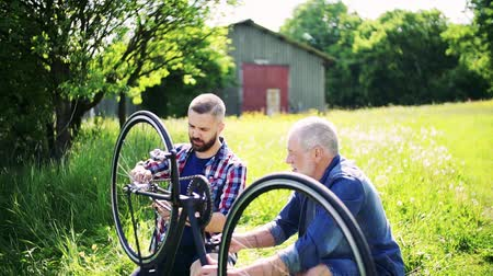 checked pattern : A senior father repairing bicycle with his adult hipster son outside on a sunny day.