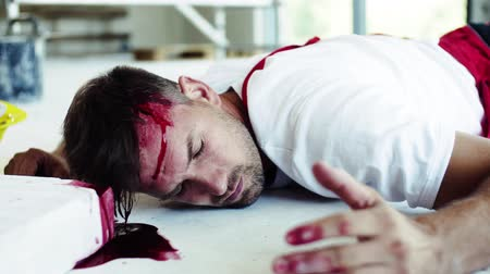 čelo : A man worker with bleeding wound on head lying on the floor after accident.