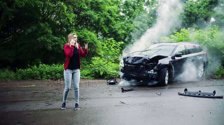 after fire : Young frustrated woman making a phone call after a car accident.