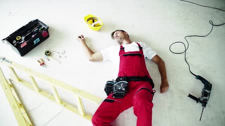 health insurance : An unconscious man worker lying on the floor after accident on the construction site.